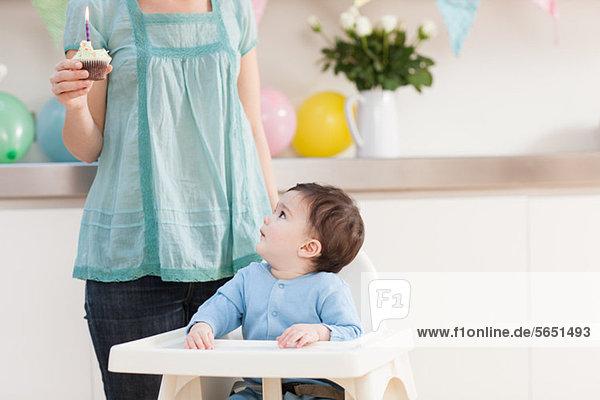 Baby Junge im Hochstuhl und aufblickend und Mutter mit Geburtstagskuchen