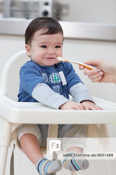 Adult feeding baby boy in high chair