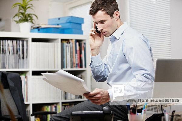 Büroangestellter sitzt auf dem Schreibtisch  auf dem Handy und sieht sich den Papierkram an.