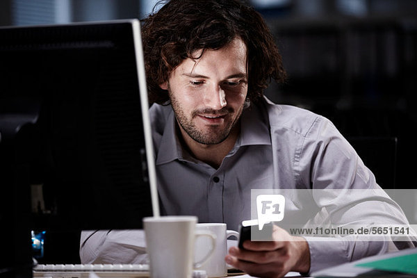 Office worker looking at cellphone in dark office