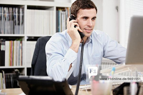 Junger Mann am Telefon und bei der Arbeit am Laptop