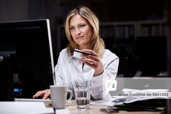 Geschäftsfrau im dunklen Büro  mit Kreditkarte online