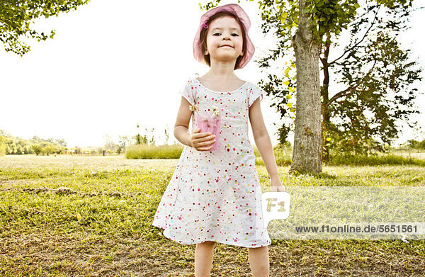 Little girl in park,  holding cup of flowers