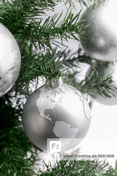 Silver globe bauble on christmas tree