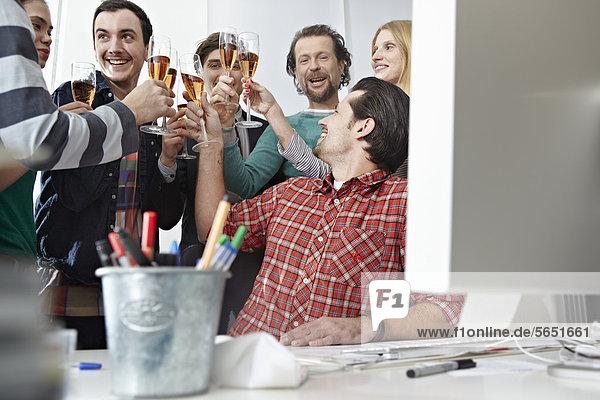 Männer und Frauen toasten mit Champagner im Büro