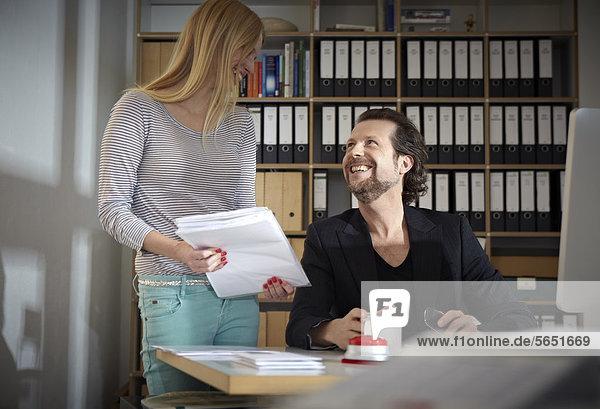 Mann und Frau  die im Büro arbeiten  lächelnd