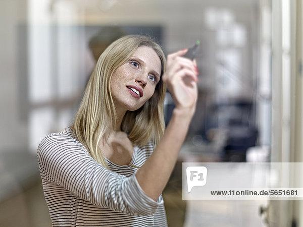 Junge Frau malt auf Glas