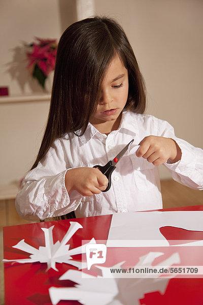 Mädchen schneiden Schneeflockenform für die Weihnachtsdekoration