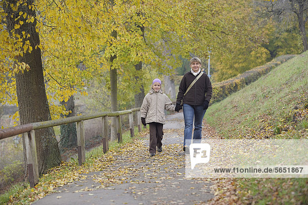 Germany  Bavaria  Mother and daughter walking on footpath in autumn