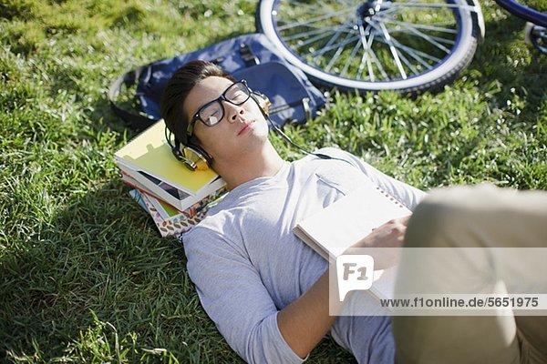 Student mit Kopfhörern im Gras