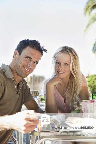 Spanien  Mallorca  Palma  Paar am Tisch sitzend im Café  lächelnd  Portrait