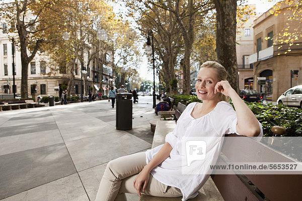 Spanien  Mallorca  Palma  Junge Frau auf Bank sitzend  lächelnd  Portrait