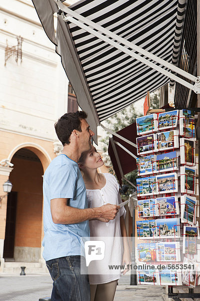 Spanien  Mallorca  Palma  Paar sucht Postkarten  lächelnd
