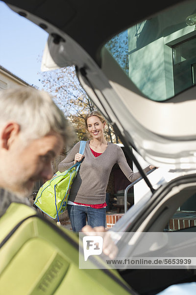 Erwachsener Mann beim Verladen des Gepäcks ins Auto  Frau steht im Hintergrund
