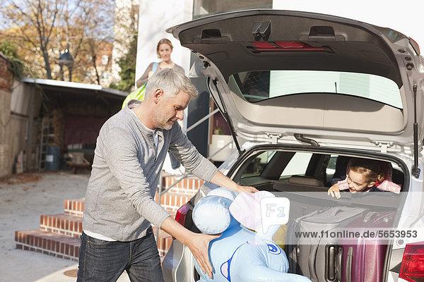 Deutschland  Leipzig  Vater beim Verladen von Gepäck ins Auto