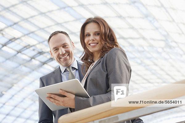 Deutschland  Leipzig  Geschäftsleute mit digitalem Tablett  lächelnd  Portrait