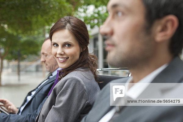 Deutschland  Leipzig  Geschäftsleute auf der Bank sitzend  lächelnd