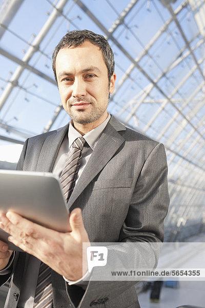 Deutschland  Leipzig  Geschäftsmann mit digitalem Tablett auf Rolltreppe  Portrait
