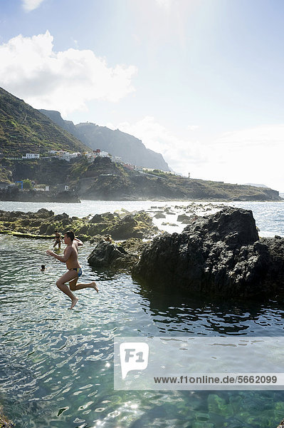 Young man jumping into the water  sea water pools in Garachico  Tenerife  Canary Islands  Spain  Europe