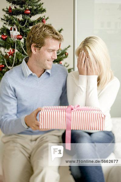 Junge Frau hält sich die Augen zu  bekommt Weihnachtsgeschenk von ihrem Partner