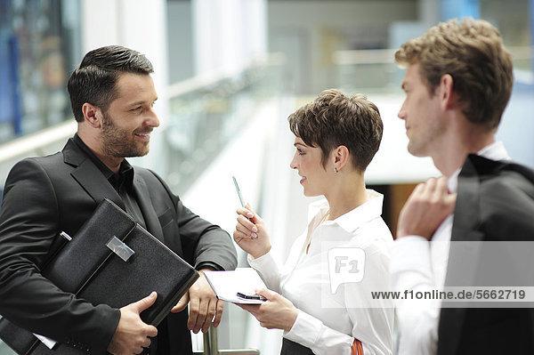 Drei junge Geschäftsleute unterhalten sich