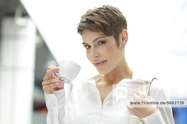 Junge Geschäftsfrau mit Tasse Kaffee