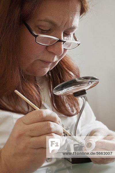 Okularistin bei Herstellung einer Augenprothese