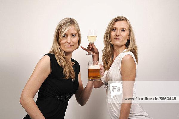 Zwillingsschwestern  eine mit einem Bierkrug  die andere mit einem Weinglas
