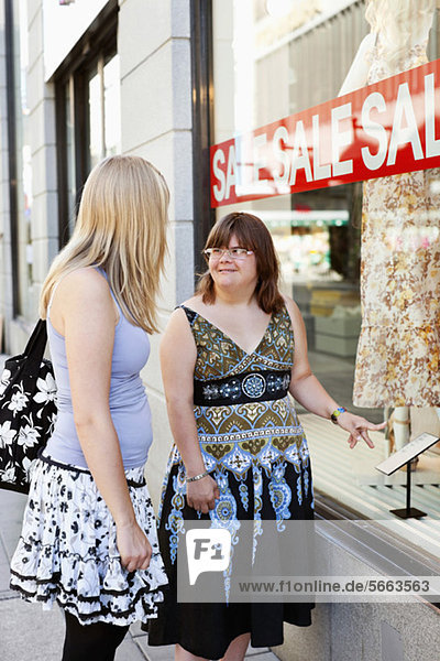 Woman with down syndrome and her personal assistant window shopping together