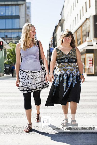 Frau mit Down-Syndrom und ihre persönliche Assistentin beim Gehen auf Zebrastreifen