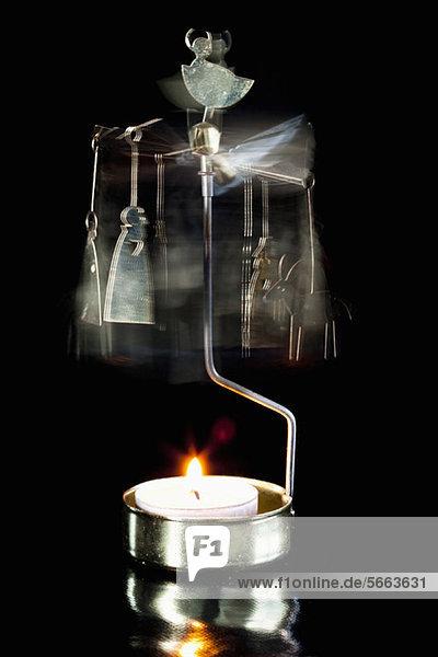 Unscharfe Bewegung des Kerzenhalters über schwarzem Hintergrund