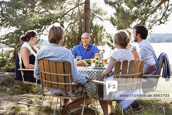 Freunde  die zusammen Spaß haben  während sie im Freien sitzen.