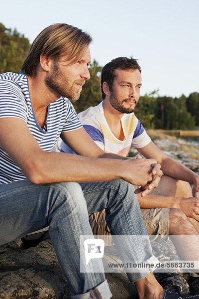 Zwei männliche Freunde  die auf dem Felsen sitzen und nachdenken.