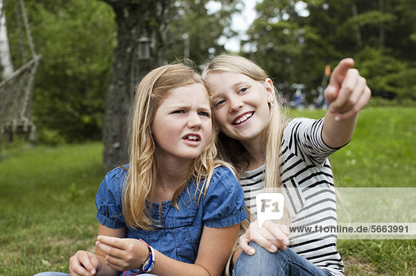 Cheerful girl showing something to sister