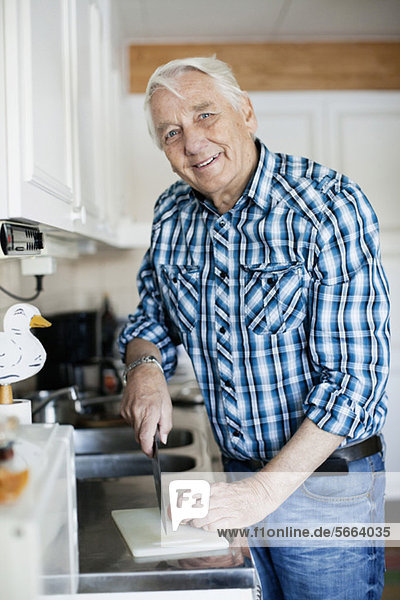 Portrait of smiling senior man with knife in kitchen