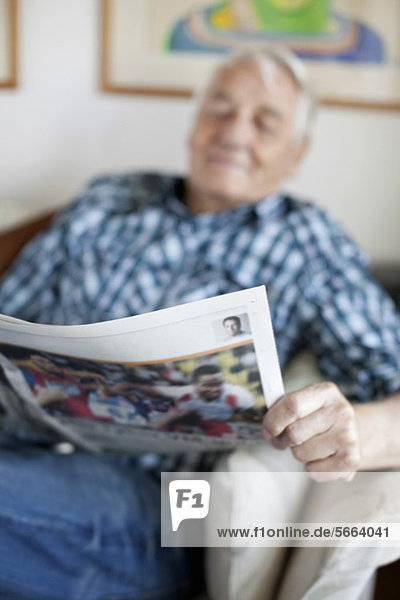 Elderly man reading newspaper while sitting in living room