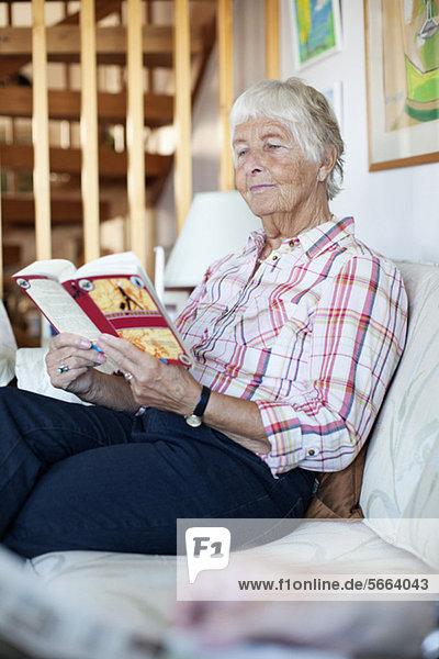 Elderly woman reading novel while sitting on sofa in living room