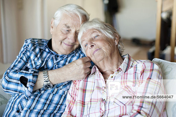 Liebender älterer Mann mit Frau auf dem Sofa im Wohnzimmer