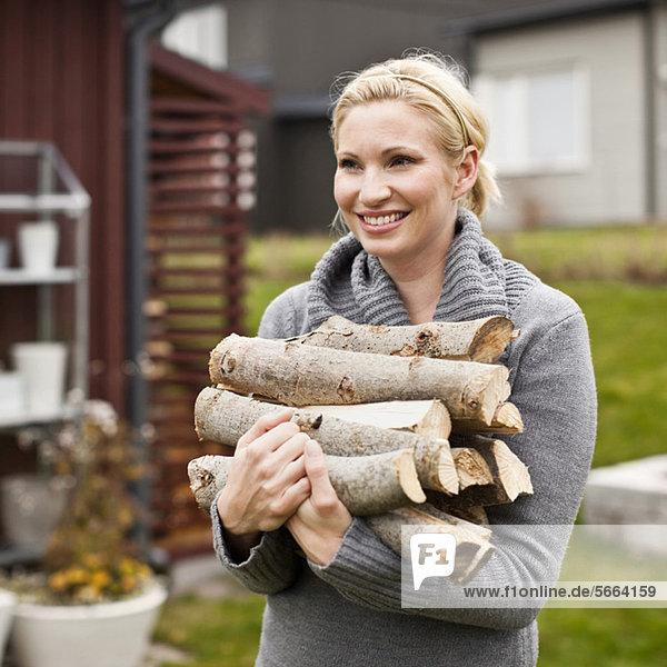 Fröhliche  erwachsene Frau mit Holz im Hinterhof