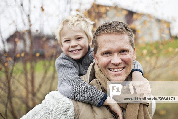 Porträt des Vaters  der seinen Sohn huckepack reitet