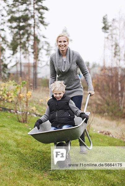 Frau schiebt ihren Sohn Schubkarre in den Hinterhof