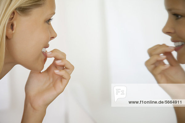 Junge Frau mit Blick auf die Zähne im Spiegel  Seitenansicht