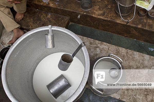 Milk in bucket with ladles  overhead view