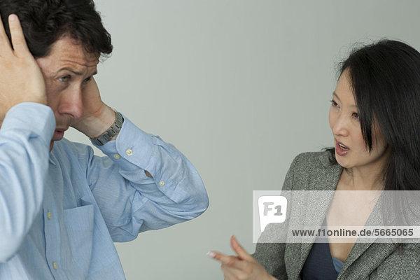 Mann und Frau streiten sich  Mann hält sich die Ohren zu.