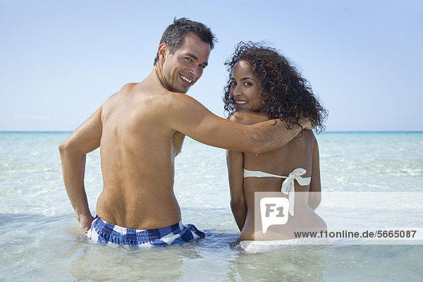 Paar Taille tief im Wasser am Strand  lächelnd über die Schultern vor der Kamera