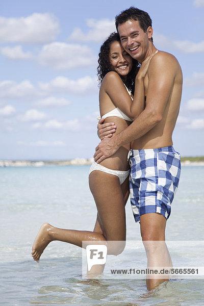 Paar am Strand im Wasser umarmend