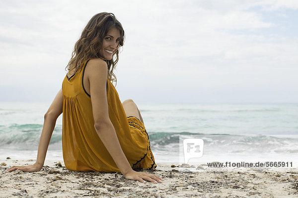 Junge Frau sitzt am Strand und schaut über die Schulter zur Kamera.