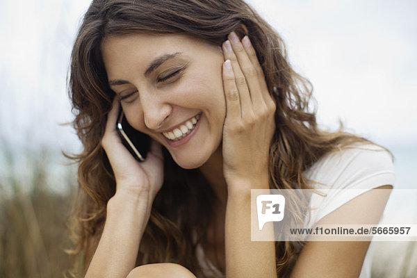 Fröhliche junge Frau am Handy  Portrait