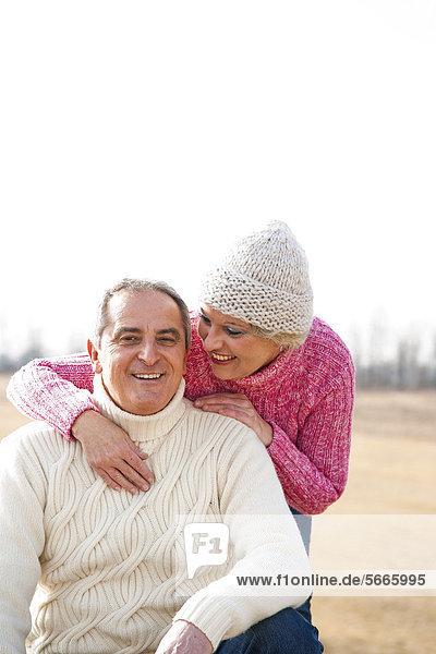 Lächelnde Frau umarmt Mann im Freien Lächelnde Frau umarmt Mann im Freien