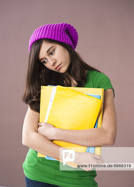 Ernste Teenagerin mit Wollmütze hält Mappen